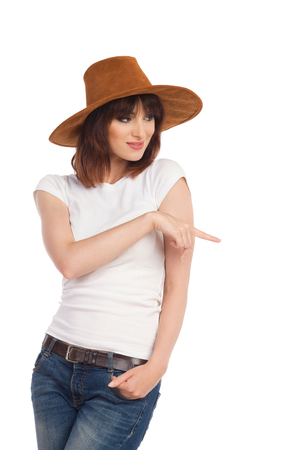 Young woman in white shirt, suede hat is standing, smiling, looking away and pointing. Three quarter length studio shot isolated on white.