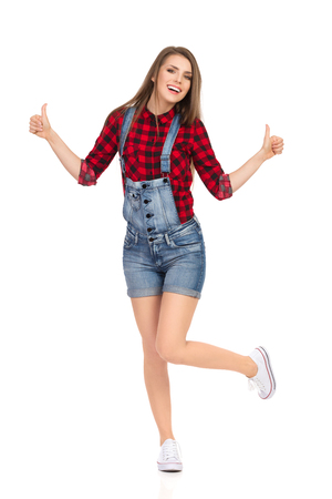Smiling young woman in red lumberjack shirt, jeans dungarees shorts and white sneakers standing on one leg and showing thumbs up. Full length studio shot isolated on white.