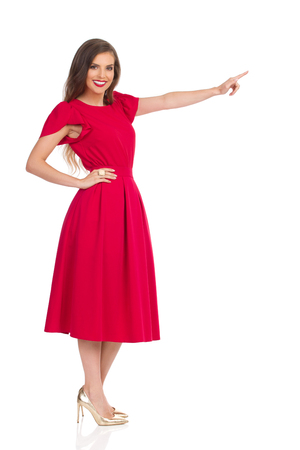 Beautiful young woman in red dress and gold high heels is looking at camera, smiling and pointing. Full length studio shot isolated on white.