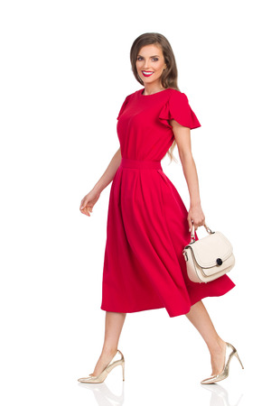 Beautiful young woman in red dress and gold high heels is holding beige purse, looking at camera, walking and smiling. Full length studio shot isolated on white.