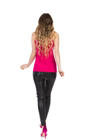 Blond woman in black leather trouser, pink high heels and top is walking. Rear view. Full length studio shot isolated on white.