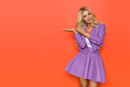 Beautiful blond woman in purple costume is holding hands raised, looking at camera and talking. Three quarter length studio shot on orange background. Imagens