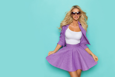 Beautiful blond woman in violet mini skirt, unbuttoned jacket and sunglasses is smiling and looking at camera. Three quarter length studio shot on turquoise background. Imagens