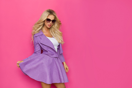 Beautiful blond woman in purple mini skirt, unbuttoned jacket and sunglasses is looking at camera. Three quarter length studio shot on pink background.