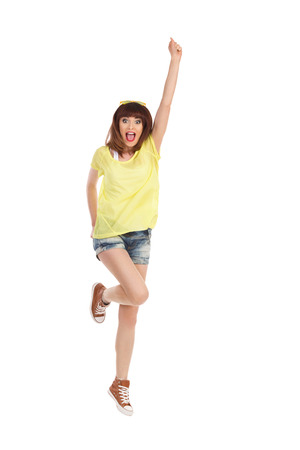 Excited young woman in yellow shirt, jeans shorts and brown sneakers is jumping with arm raised. Full length studio shot isolated on white.