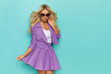 Beautiful blond woman is posing in purple mini skirt, jacket and sunglasses. Three quarter length studio shot on turquoise background.