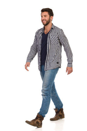 Walking man in boots, jeans and unbuttoned, lumberjack shirt, smiling and looking away. Full length studio shot isolated on white. Reklamní fotografie