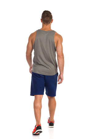 Rear view of walking fit man in gray tank top, blue shorts and orange sneakers. Full length studio shot isolated on white. Stock Photo