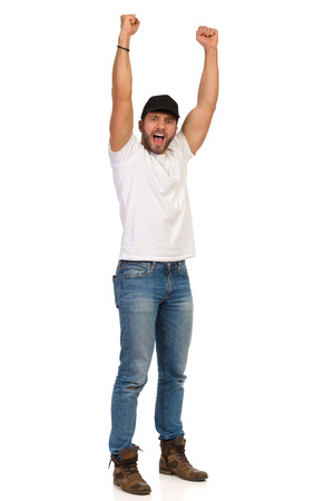 Man in jeans, white t-shirt and black cap is standing with arms raised, looking at camera and shouting. Full length studio shot isolated on white.