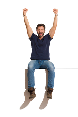 Young man in boots, jeans and blue shirt is sitting on a top, rising arms, looking at camera and shouting. Full length studio shot isolated on white. Stock Photo