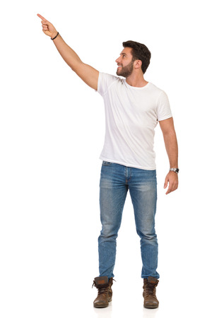 Young man in jeans and white t-shirt is standing, smiling, pointing up and looking away. Front view. Full length studio shot isolated on white. Banque d'images