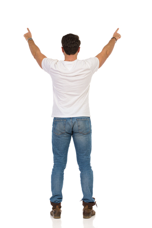 Young man in jeans and white t-shirt is standing with arms outstretched and pointing. Rear view. Full length studio shot isolated on white.