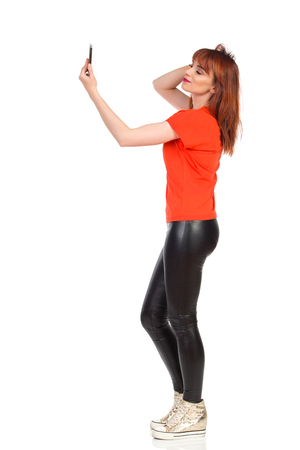 Young woman in orange t-shirt, black leggings and gold sneakers is standing, holding cell phone and taking selfie. Side view. Full length studio shot isolated on white. Banque d'images