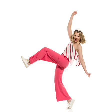Young woman in red wide leg trousers and striped top is funny walking with arms outstretched. Full length studio shot isolated on white.