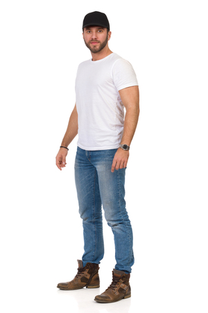 Man in jeans, white t-shirt and black cap is standing relaxed and looking at camera. Full length studio shot isolated on white.
