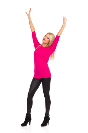 Beautiful blond woman in black leggings, high heels and pink sweater is standing, holding arms raised and looking away. Full length studio shot isolated on white.