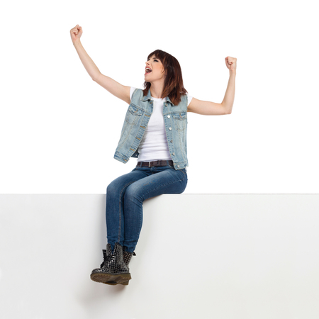 Young woman in jeans vest and black boots is sitting on a top, flexing muscles, looking away and shouting. Full length studio shot on white background. Imagens