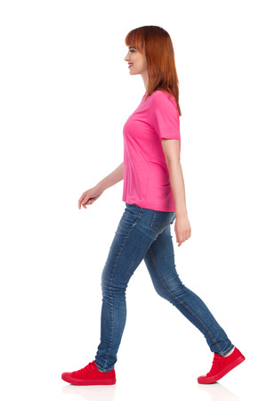 Smiling young woman in pink shirt, jeans and red sneakers is walking and looking away. Side view. Full length studio shot isolated on white.