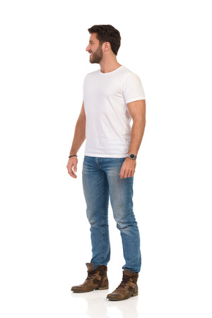 Smiling man in jeans and white t-shirt is standing and looking away. Side view. Full length studio shot isolated on white.