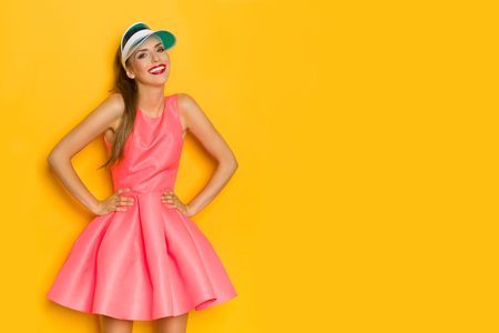 Beautiful young woman in pink mini dress and blue sun visor posing with hands on hip, looking at camera and smiling. Three quarter length studio shot on yellow background.