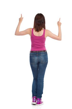 Rückansicht der jungen Frau in Magenta-Trägershirt, Jeans und Turnschuhen, stehend und oben zeigend. Studioaufnahme in voller Länge isoliert auf weiss.