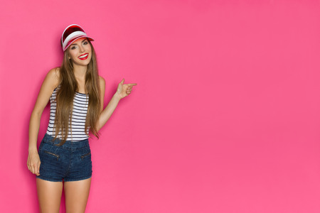 Beautiful girl in striped shirt, jeans shorts and red sun visor cap is pointing and smiling. Three quarter length studio shot on pink background.