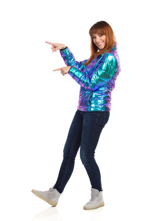 Young woman in vibrant and shiny down jacket, jeans and sneakers is standing, looking at camera, pointing and smiling. Side view. Full length studio shot isolated on white.