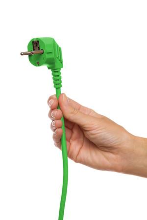 Énergie éco-énergétique. Gros plan de la main de la femme tenant une prise électrique européenne verte. Studio tourné isolé sur blanc.
