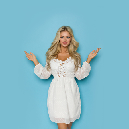 Beautiful blond woman in white lace dress is holding hands raised, presenting and looking at camera. Three quarter length studio shot on blue background.