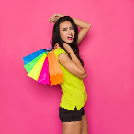 Felice bella giovane donna in camicia verde vibrante e pantaloncini neri sta tenendo borse della spesa colorate sulla sua spalla e shoutng. Studio di tre quarti di lunghezza girato su sfondo rosa. Archivio Fotografico