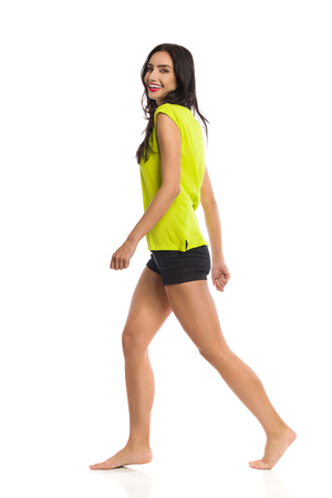 Young woman in green shirt, black shorts is walking barefoot, looking at camera and laughing. Side view. Full length studio shot isolated on white. Stock Photo