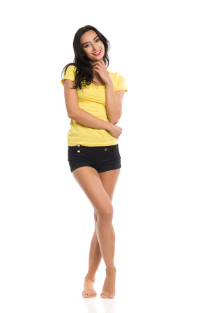 Young woman in yellow shirt, black shorts is standing barefoot with legs crossed, looking at camera and smiling. Front view. Full length studio shot isolated on white.