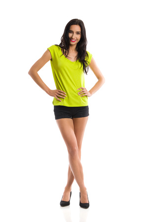Young woman in green shirt, black shorts and high heels is standing with legs crossed, looking at camera and smiling. Front view. Full length studio shot isolated on white.