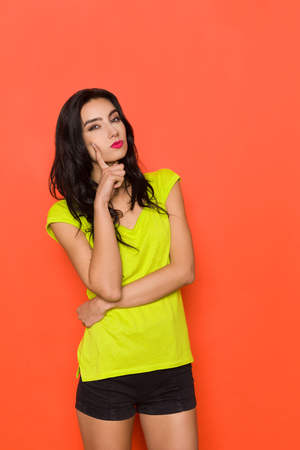 Serious young woman in green shirt and black shorts is looking at camera, holding finger on chin and thinking. Three quarter length studio shot on orange background.