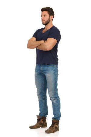 Ernstige knappe man in jeans, laarzen en blauw t-shirt staat met gekruiste armen en kijkt weg. Volledige lengte studio opname geïsoleerd op wit.