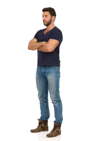 Serious handsome man in jeans, boots and blue t-shirt is standing with arms crossed and looking away. Full length studio shot isolated on white.