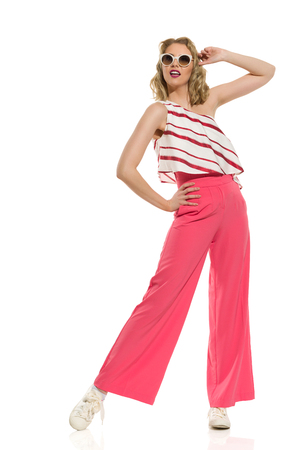Stylish young woman in red wide leg trousers and sunglasses is posing with legs apart. Full length studio shot isolated on white.