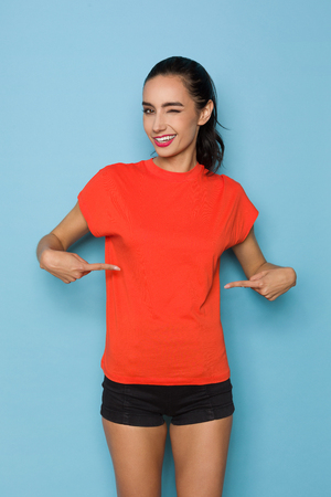 Beautiful young woman in orange t-shirt is pointing at herself and winking. Three quarter length studio shot on blue background. Banco de Imagens