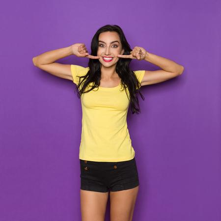 Jonge vrouw in geel shirt en zwarte korte broek wijst naar haar glimlach. Driekwart lengte studio opname op paarse achtergrond.