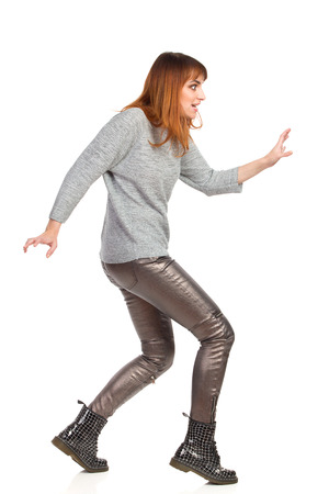 Spooky young woman in gray blouse, shiny pants and black boots is walking with arms outstretched and looking away. Side view. Full length studio shot isolated on white.