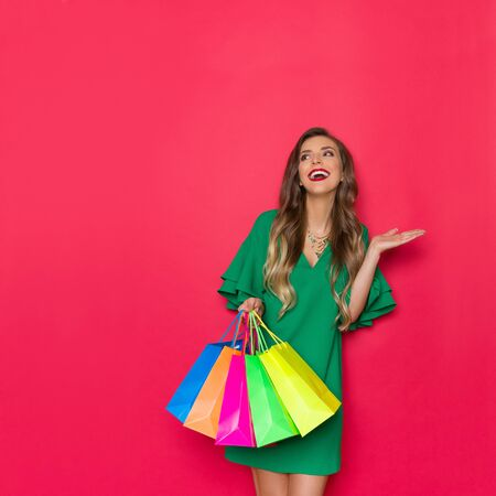 Happy elegant young woman in green mini dress is holding colorful shopping bags, looking away, laughing and presenting. Three quarter length studio shot on red background.