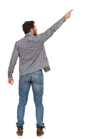 Man in jeans, boots and lumberjack shirt is standing with arm raised, pointing up and looking. Rear view. Full length studio shot isolated on white. Foto de archivo