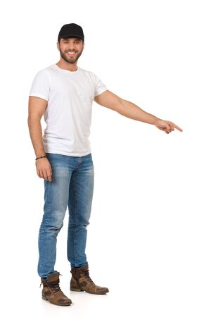 Handsome young man in jeans, white t-shirt and black cap is standing looking at camera and pointing down. Full length studio shot isolated on white. Foto de archivo
