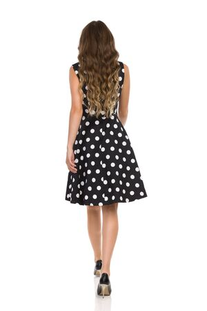 Rear view of walking beautiful young woman in black cocktail dress in polka dots and high heels. Full length studio shot isolated on white.