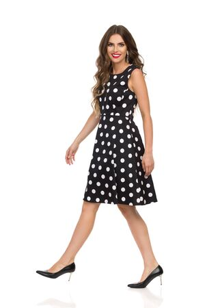 Beautiful young woman in black cocktail dress in polka dots and high heels is walking, looking at camera and smiling. Side view. Full length studio shot isolated on white.