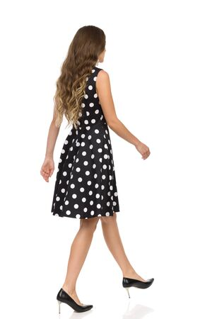 Walking beautiful young woman in black dotted cocktail dress and high heels. Rear side view. Full length studio shot isolated on white.