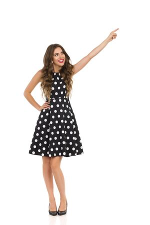 Happy beautiful young woman in black cocktail dress in polka dots and high heels is smiling, pointing and looking away. Full length studio shot isolated on white.
