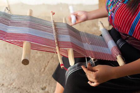 Gros plan des mains d'une femme tissant sur un vieux métier à tisser en bois.