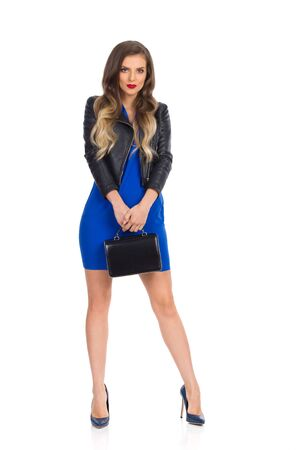 Beautiful young woman in blue mini dress, leather jacket and high heels is holding black purse and looking at camera. Full length studio shot isolated on white. Reklamní fotografie