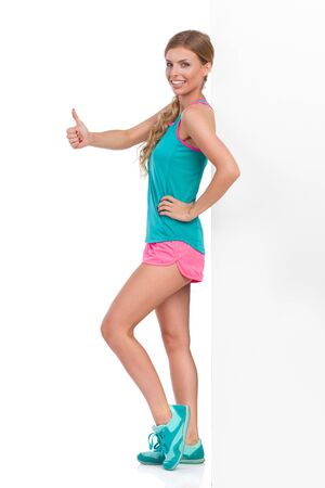 Smiling beautiful young woman in pink shorts, turquoise tank top and sneakers leaning against wall and showing thumb up hand sign. Side view. Full length studio shot isolated on white.